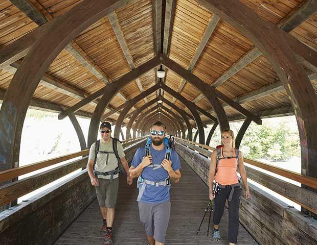 Drei Wanderer auf Holzbrück die über Inn verläuft.